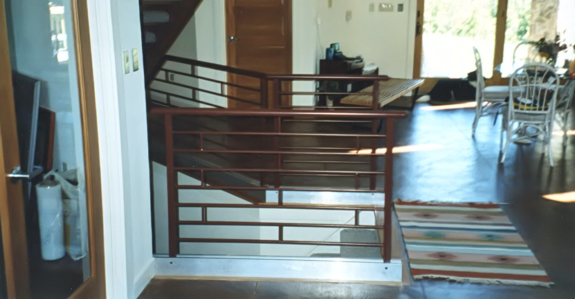 a railing with bent interior wood distressed handrail and iron finished art base railings