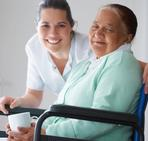 Image of older female adult sitting in wheel chair smiling, Women is accompanied by female medical staff also smiling.