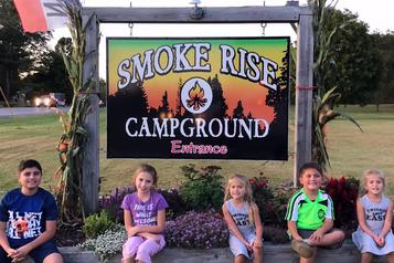Children sitting in front of Smokerise Campground sign at entrance to park.