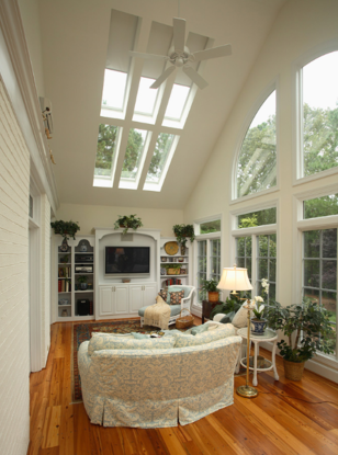 Sunroom with blinds on skylights and entertainment center
