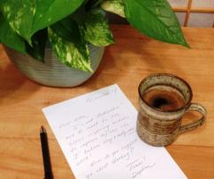 ellie hadsall books, cosmic gathering, coffee cup, letter, plant, desk