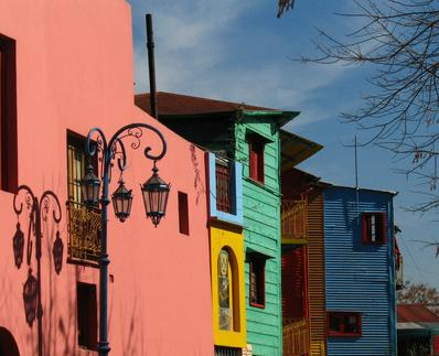 picture of a pink blue and turquoise house in rows