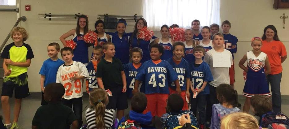 football players and cheerleaders at assembly