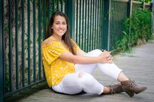 photo by shrinking buffalo productions - high school senior female sitting in yellow and white against greet railing