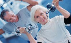 Mature Couple exercising with weights in a private fitness retreat for toning, muscle conditioning and strength..