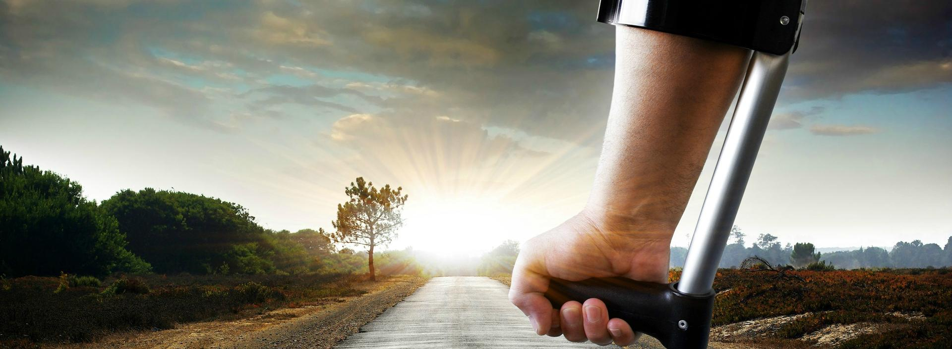 Forefront: Right hand gripping hand rest of Canadian Crutch; Background: country road leading to horizon against setting sun.