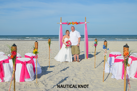 A bride and groom pose in front of their St. Augustine Beach Wedding Packages decor.