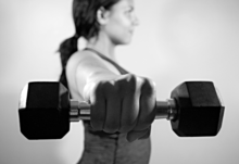 A woman in athletic attire lifting a weight towards the foreground in a lateral raise.
