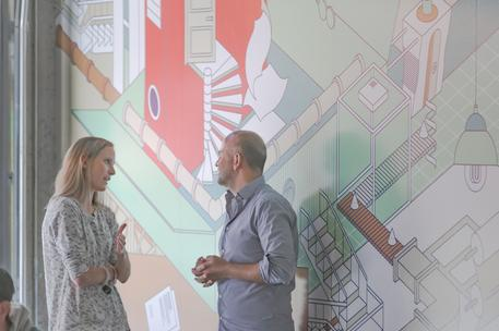 male and female tech employees chatting by mural