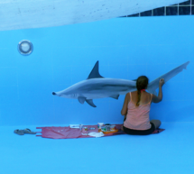 Savanna Redman painting a shark mural in a swimming pool