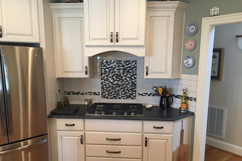 Custom tile backsplash above the cooktop. Stainless steel appliances and white cabinets topped with granite.