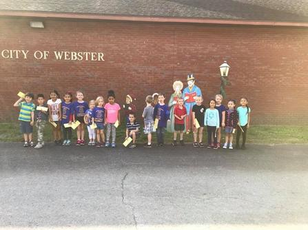"A line of young children in front a brick wall with ""City of Webster"" on it in white text."