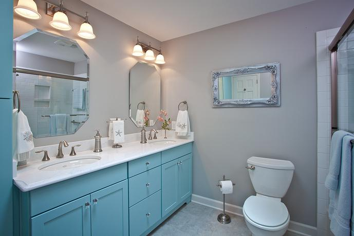 Raised double vanities with quartz countertops and comfort height toilet in guest bathroom after remodel
