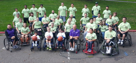 Group of wheelchair users and non-wheelchair users, many of whom are wearing green shirts at a Dribble on Wheels basketball camp