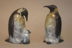 a pair of penguins with a chick