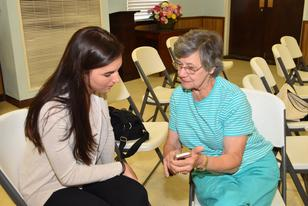 Photo of a FriendShip volunteer helping a member learn to use her cell phone.