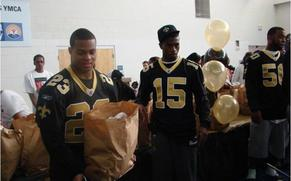 Picture of the Saints football players handing out Free turkeys.