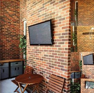 Flat screen television installed on brick wall on a patio. power and HDMI installed by carolina custom mounts in charlotte nc