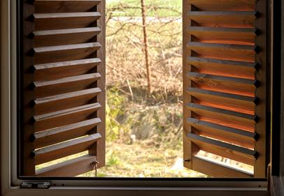 open wood shutters showing the beautiful nature outside