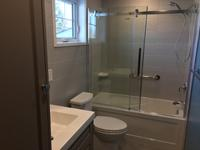 This bathroom renovation features a custom full height linen cabinet which also houses a pull-out hamper. Four recessed LED pot lights were installed, which also allowed for a custom full height mirror.