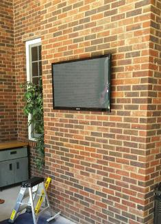 Flat Screen TV mounted on brick outside porch, Carolina Custom Mounts, Charlotte NC best professional TV mounting service