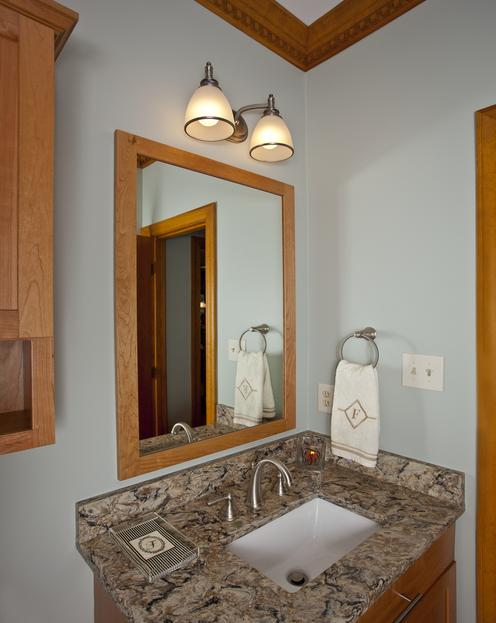 Powder room with natural cherry cabinets, framed mirror and quartz countertops