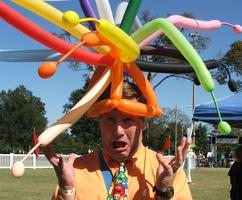 Company Picnic Balloon Artist showing off a colorful balloon hat.