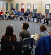 Group counseling session with over 30 people sitting around in a circle on chairs.