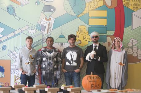 group of tech employees costume contest in front of mural bay area