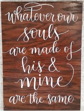 """Whatever our souls are made of his & mine are the same"" quote written in white modern calligraphy on dark wood for wedding."