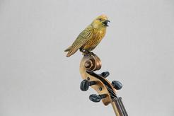 a Yellow Warbler sitting atop a violin