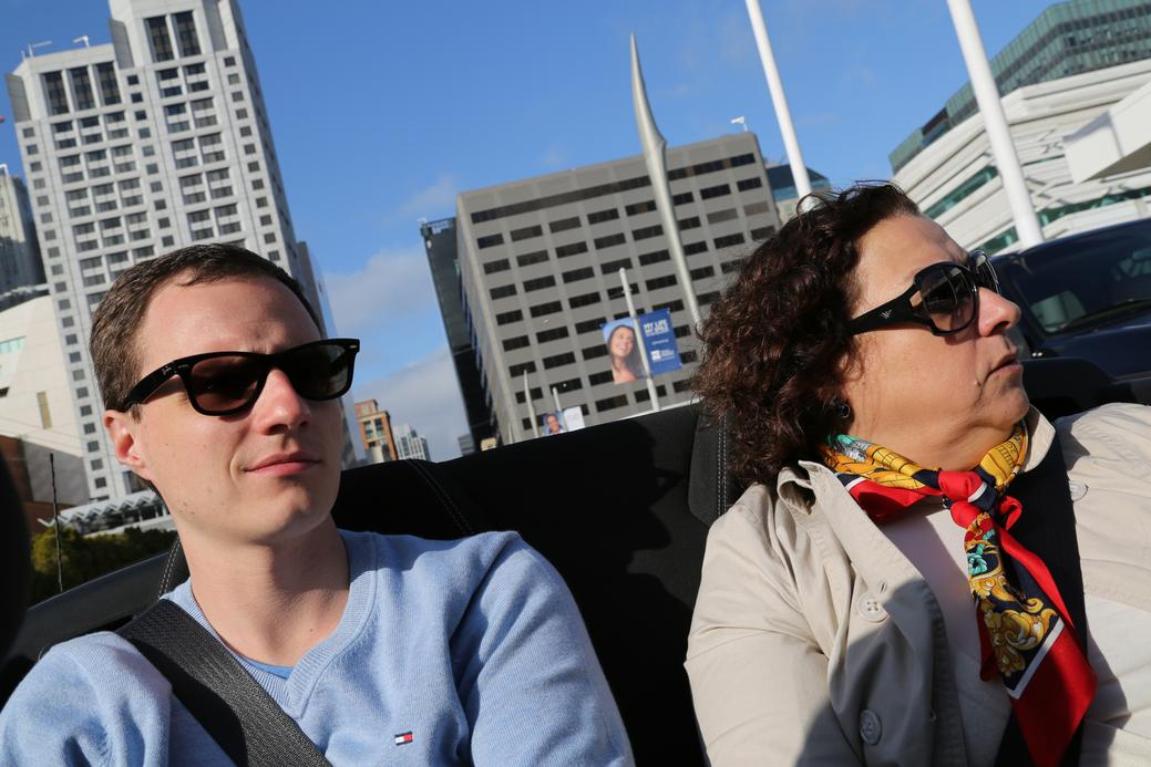 two people in convertible car blue sky