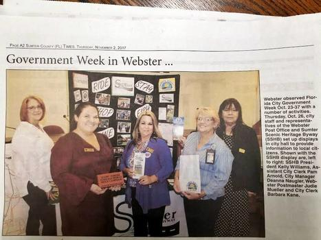 "A newspaper article named ""Government Week in Webster"" shows city employees posing with a black display board."