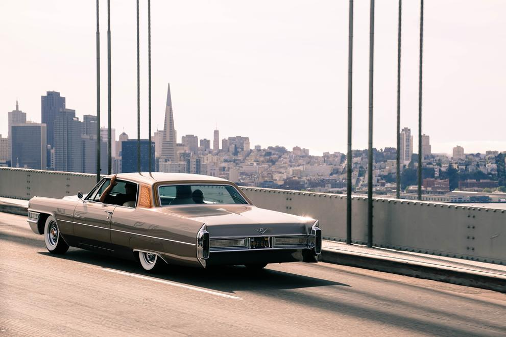 vintage car corssing bay bridge overlooking san francisco skyline landscape