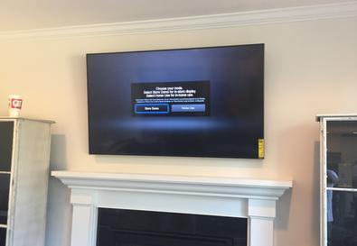 65 inch flat screen 4k TV mounted on fireplace by Carolina Custom Mounts in Charlotte NC