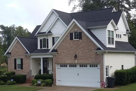 5 inch Seamless gutter and 3x4 downspouts with LeaFree gutter protection system installed on Wake County NC home