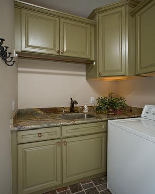 Beautiful Showplace cabinetry topped by rainforest granite in this laundry room transformation