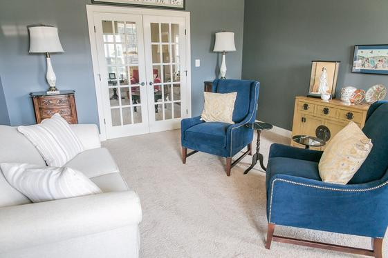 Contemporary interior design often includes mixing the old with the new as can be seen in this living room. Navy velvet chairs sit across a beautiful, light gray sofa. New lamps, trimmed in copper, sit atop antique tables.