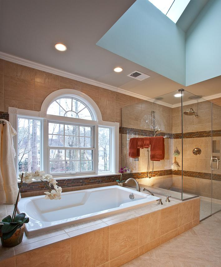 Bathtub with custom tile surround, palladium window, curbless shower stall, hand held shower spray are just some of the elements in this bathroom remodel.
