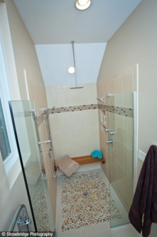 Curbless shower stall with pebble tiles, rain shower head and body sprays