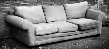 picture of a couch in an alley against a brick wall