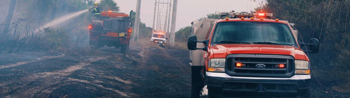 Attack truck and brush truck fighting a brush fire with a support vehicle off in the distance