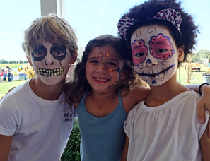 Three children with they're faces painted. The Boy on the left has a full face of skeleton facepaint. The girl in the middle has a stem with little flowers coming down her forehead and nose and across her right cheek. And the girl on the right has a full face of female skeleton facepaint with pink flowers around her eyes.