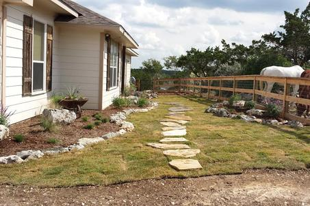 A flagstone walkway in San Antonio texas landscaped by wilson landscape with a large flowerbed on the left side and a smaller flowerbed on the right side and Sod grass underneath