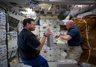 NASA astronauts Greg Chamitoff (left), mission specialist, and Mark Kelly, mission commander, are unpacking canisters of the Group Activation Pack.