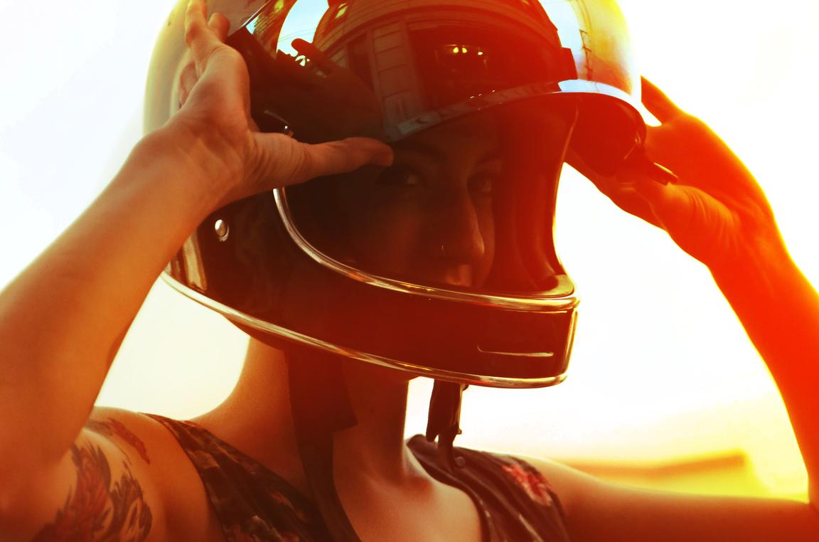 young biker woman with helmet lifestyle orange sunset high exposure