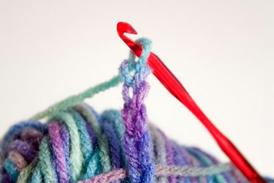 An example of a crochet needle being used with some purple and blue yarn.