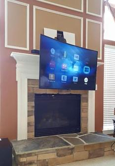 Carolina Custom Mounts of Charlotte Flat screen tv mounting services.  Picture of Curved TV mounted over Fireplace with pull down fireplace mount.