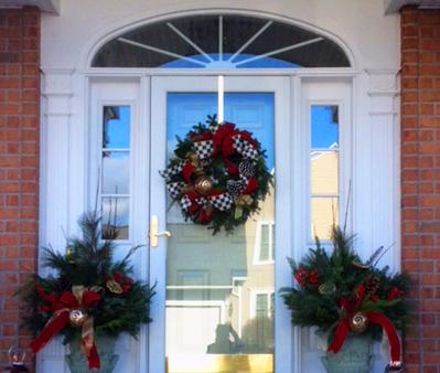 Front door of a home in Rochester NY with wreath and two floral arrangements