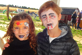 2 children with they're faces painted. the Girl has ghosts on her face and the boy has vampire face painting